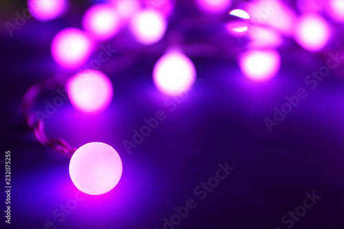 Glowing Christmas lights on dark background - 232075255