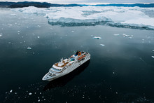 Cruise Ship In The Arctic Ocean In Front Of An Ice Berg