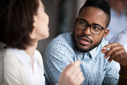 Obraz Close up of multiracial colleagues chat talking or discussing something in office, black man speak with female coworker negotiating about business project, having conversation. Cooperation concept - fototapety do salonu
