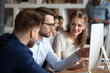 canvas print picture Diverse millennial employees coworking discussing business project or idea in shared office, smiling colleagues work together at pc, male worker explain to coworkers pointing at computer screen