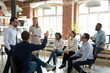 canvas print picture - Ambitious male employee raise hand ask question to female presenter at meeting, man show activity at teambuilding with multiethnic colleagues, diverse workers brainstorm at office education briefing