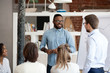 canvas print picture Multiethnic colleagues talk making flipchart presentation to coworkers during meeting, African American coach present project interacting with employees, diverse workers brainstorm at training