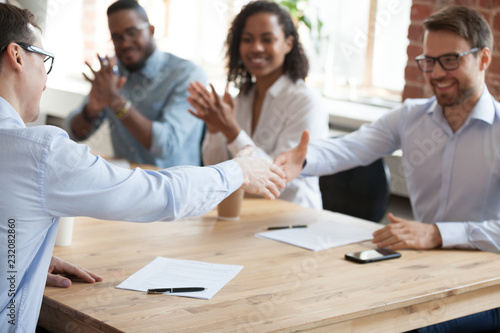 Photo Smiling business partners shake hands after successful negotiations in office, excited male workers handshake greeting with employment, happy employees get acquainted at meeting