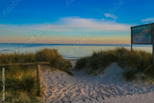 A beach entrance through the dunes, beachgrass and powdery sand of Fehmarn island in Germany at dusk Canvas-taulu