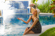 lifestyle portrait of young happy and beautiful tourist woman in Summer hat posing relaxed and smiling cheerful at tropical resort swimming pool in holidays travel