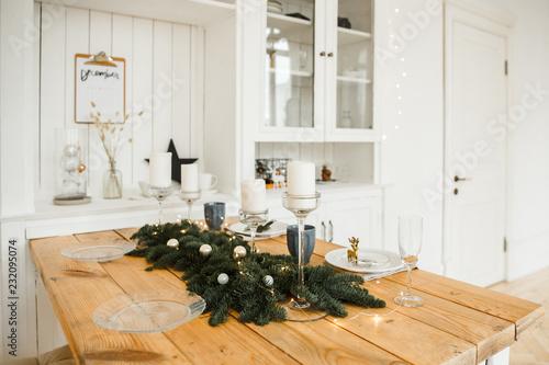 Zdjęcie XXL Ustawienie świątecznego stołu. Jasny salon z drewnianym stołem, ozdobiony świecami, gałęzie jodły i świąteczne girlandy.