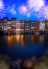 Fototapeta Houses facades over canal with reflections illuminated at blue night with fireworks, Amsterdam, Netherlands