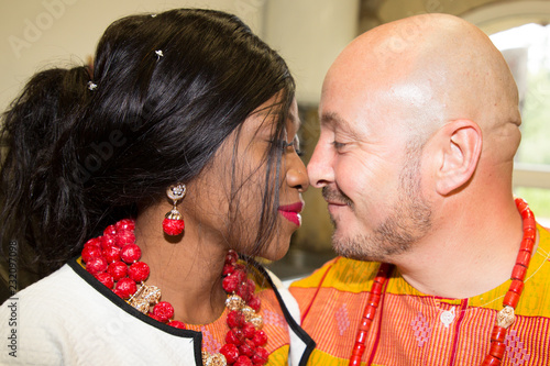 African Wedding Bride in traditional outfit with caucasian groom kiss and love