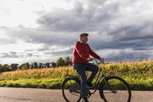 Senior Man Riding Bicycle On Country Lane