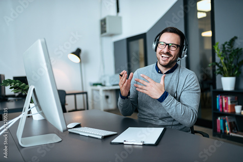 Fototapety, obrazy: Happy young customer service operator talking via headset in modern office.