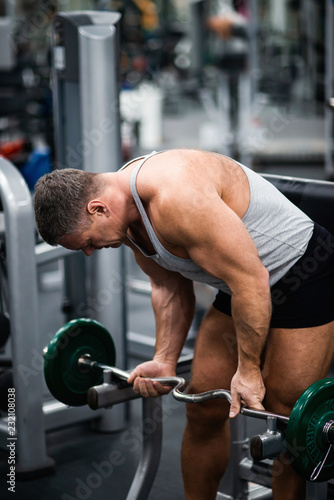Poster Fitness athletic man trains in the gym. Training biceps with a barbell