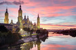 A landscape of Pilar Cathedral and Santiago Bridge reflecting in the Ebro river at sunset, after a storm, in a cloudy autumn, in Zaragoza, Spain