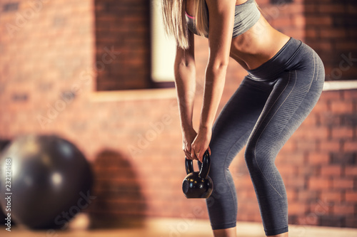 Pinturas sobre lienzo  Attractive woman with slim body in gym holding a kettlebell
