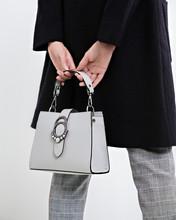 Girl Holding A Handbag In Hand...