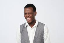 Young African Man Wearing White Shirt And Vest In Good Mood Flirting, Smiling Broadly And Winking