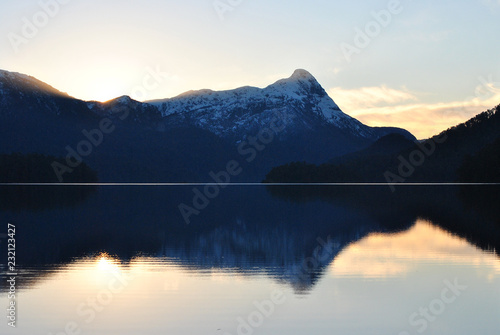Aluminium Prints The sun hidden behind blue mountains at sunset or sunrise, with some orange glow witth clouds and clear blue sky, with clear still water with the lake in the foreground reflecting the background