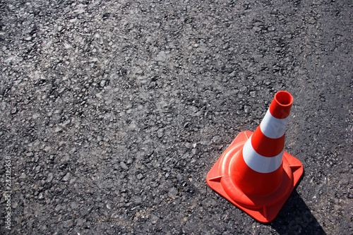 Fotografie, Obraz  traffic cone, with white and orange stripes on gray asphalt, copy space