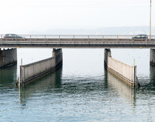 Concrete Bridge Over Water With A Train Line And Road Running Parallel And A Boat And Ship Passageway Below And Two Cars Heading Toward Each Other