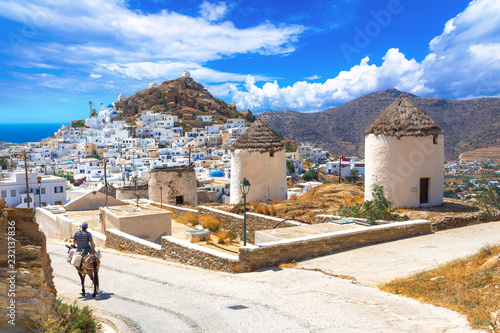 Fototapeta Traditional houses, wind mills, churches  and donkey in Ios island, Cyclades, Greece
