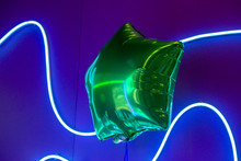 Green Star Balloon With A Neon Light Behind It