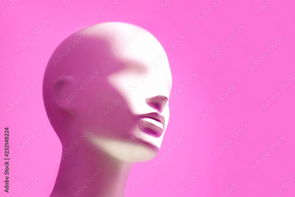 Fototapeta Head of white mannequin on pink background. Faceless girl.