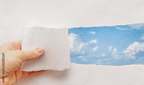Fotografía  blue sky torn paper hand