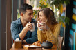 canvas print picture - Young couple in love sitting in a cafe, drinking coffee