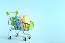 Small Paper Shopping Bags With Shopping Cart On Blue Background