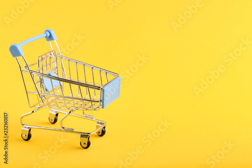 Fotografía  Shopping cart on yellow background