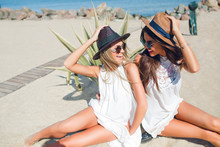 Two Attractive Brunette And Blonde Girls With Long Hair Are Sitting On The Beach Near Sea. They Wear Hats, Sunglasses And White Dresses. They Are Holding Hats And Smiling To Each Other.