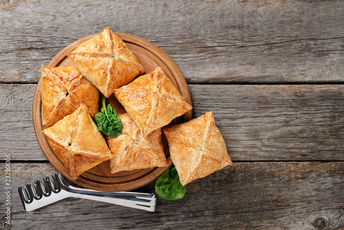 Fotografía  Puff pastry squares filled with potato, cheese and spinach on wooden table