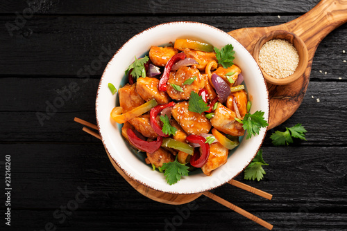 Tablou Canvas Stir fry with chicken, vegetables, soy sauce and sesame on black wooden background