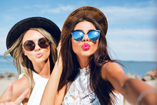 Close-up Selfie-portrait Of Two Attractive Brunette And Blonde Girls With Long Hair Standing On The Beach. They Wear Hats, Sunglasses And White Dresses. They Are Making A Kiss To The Camera.