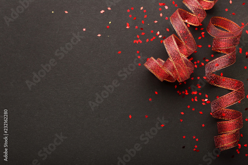 Foto  Red ribbons with confetti on black background
