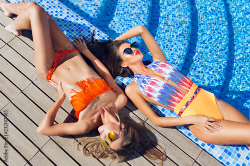 Obraz na plátně Two attractive blonde and brunette girls with long hair are lying on flor near pool