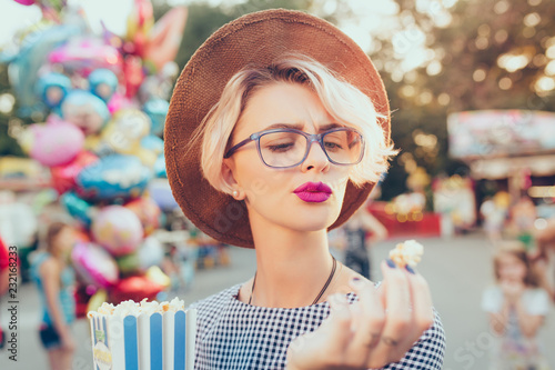 Closeup portrait of blonde girl with short haircut in amusement park on baloons background. She wears checkered dress, hat, glasses, purple lips. She is looking at popcorn.