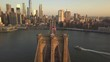 AERIAL: View over Brooklyn Bridge towards Manhattan with American Flag at Sunrise/Sunset (4K)