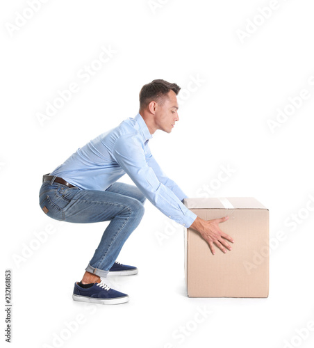 Cuadros en Lienzo Full length portrait of young man lifting heavy cardboard box on white background