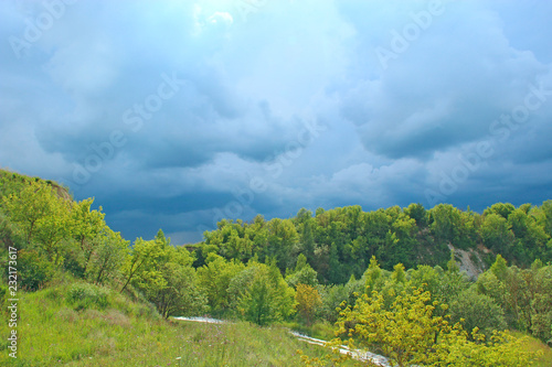 Landscape with thundercloud over green forest. Stormcloud above green vegetation