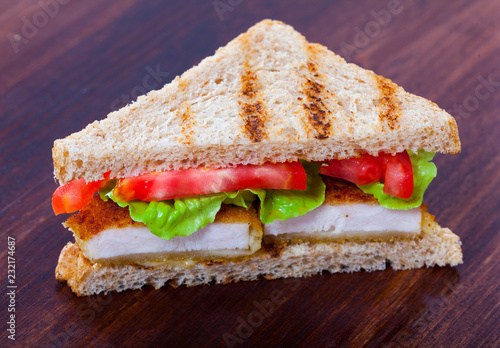 Sandwich with bread, chicken nuggets, tomatoes and lettuce