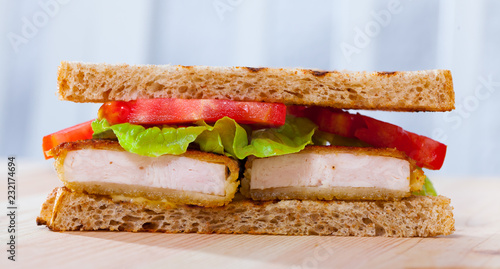 Delicious sandwich with fried chicken nuggets, lettuce and tomatoe
