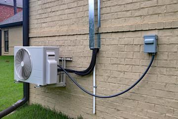 Mini split sustav klima uređaja pored kuće s opečnim zidom