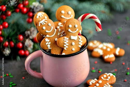Foto auf Leinwand Kekse Christmas gingerbread cookie man in a mug decorated with icing