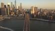 AERIAL: Flight over Brooklyn Bridge towards Manhattan with American Flag at Sunrise/Sunset (4K)