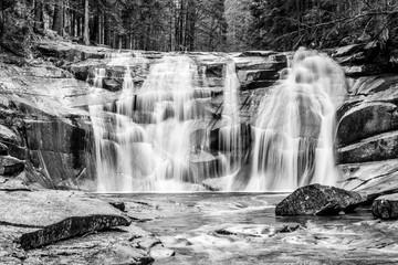 FototapetaMumlava waterfall in autumn, Harrachov, Giant Mountains, Krkonose National Park, Czech Republic. Black and white image.