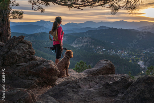 Fototapeta A hispanic woman is hiking with a dog, at sunset, in the Rocky Mountains near Denver, Colorado, USA obraz