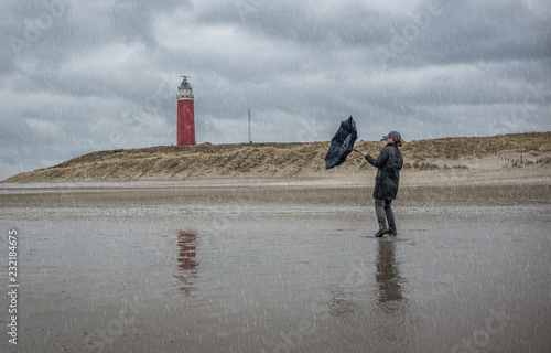 Fotografie, Tablou  Woman struggling with umbrella in stormy weather, on Monday 27 February 2017, Texel, the Netherlands