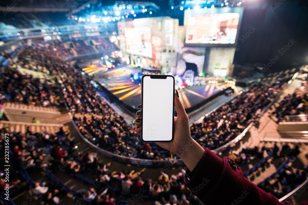 Fototapeta Woman's hands using digital application on the mobile smart phone at esport event at big arena. Copy space.