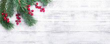 Christmas Background With Tree Branches And Holly Berries. White Wooden Table. Snowfall Drawing Effect. Top View. Copy Space
