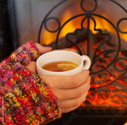 Spoed Foto op Canvas Thee Woman resting with cup of hot drink near fireplace. Woman hands with mug of tea. Colorful sweater. Fire. Winter concept